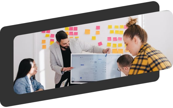 group of workers around a whiteboard in an office
